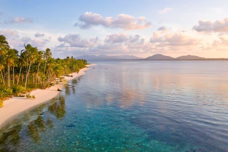 Strand tropisch eiland bij zonsondergang Een strand met wit zand en palmen in de avond royalty-vrije stock afbeeldingen