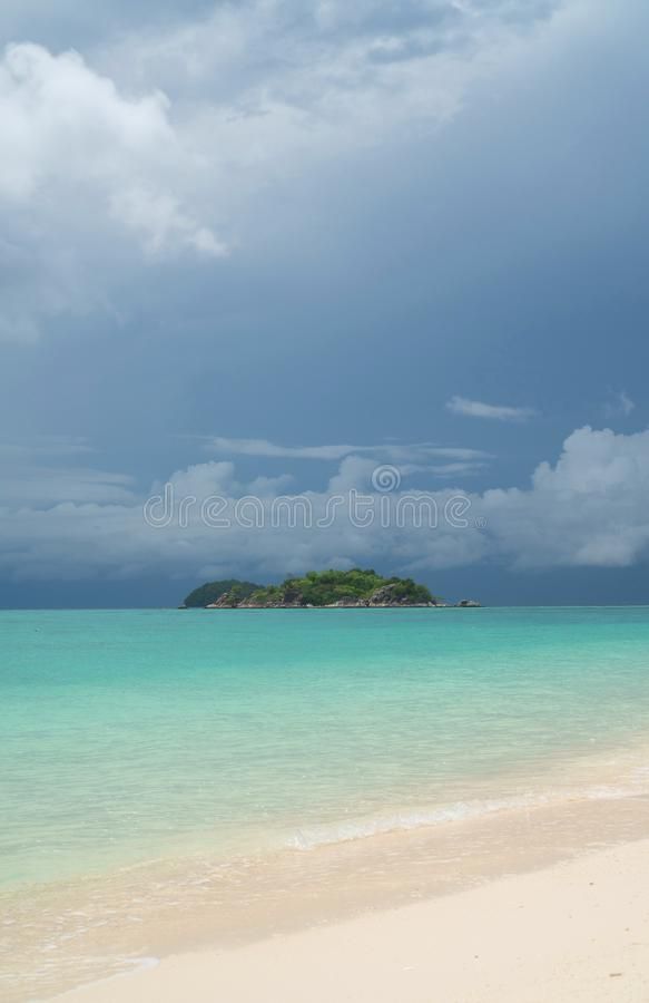Strand und Meer mit kleiner Insel ?ber bew?lktem Himmel lizenzfreies stockbild