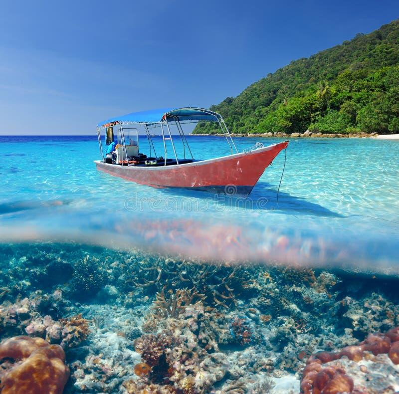Strand und Motorboot mit Korallenriffunterwasseransicht stockbild