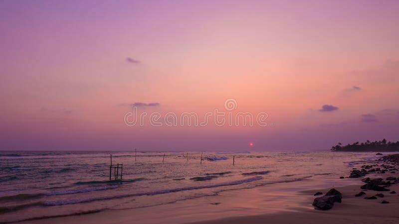 Strand und Sonnenunterganghimmel lizenzfreie stockbilder