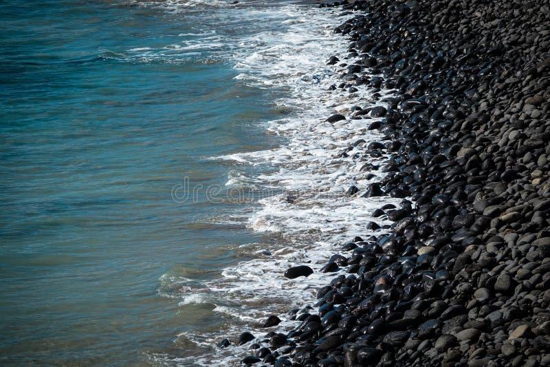 Strand van zwarte vulkanische rotsen bij de kustlijn stock foto's