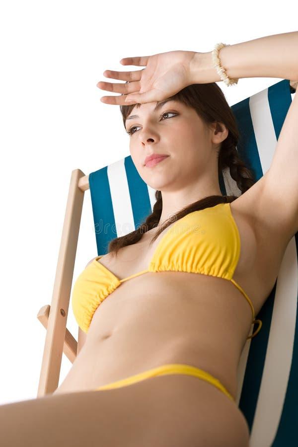 Strand - vrouw die in bikini op deckchair zonnebaadt stock afbeeldingen