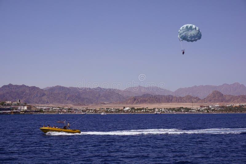 Strandactiviteit: het parasailing, hoge snelheidsboot trekt een mens op een valscherm Overzees en bergen op de achtergrond stock fotografie
