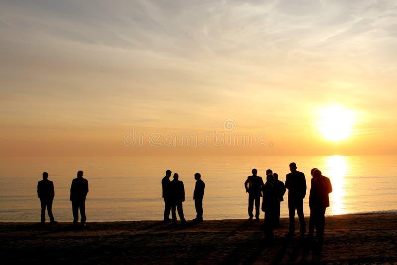 strandaffären bemannar silhouetten royaltyfri foto