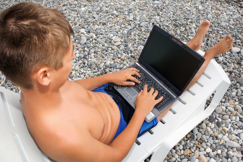 strandbärbar dator som ser den reclining skärmen för man royaltyfria foton