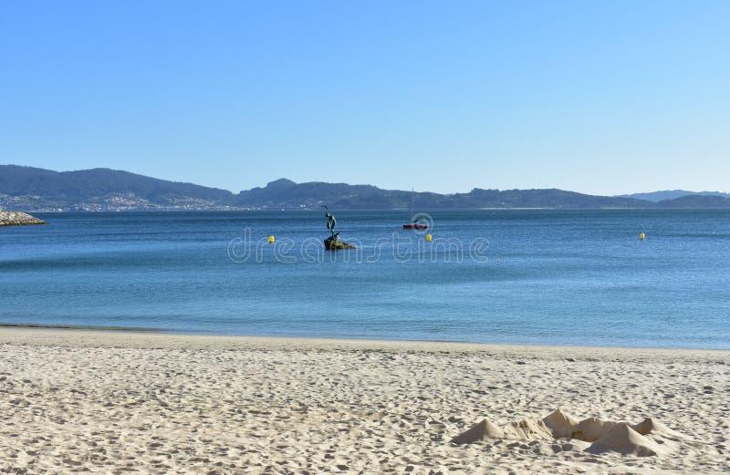 Strandbakgrund: Strand i en fjärd med slotten som göras av sand Ljus sand, klart vatten, blå himmel Solig dag Sanxexo, Galicia, S royaltyfri fotografi