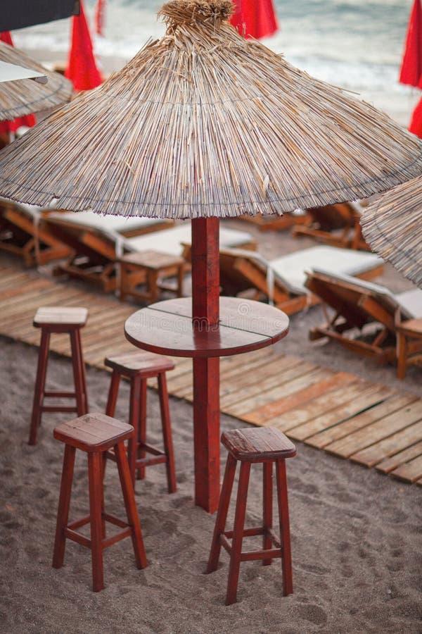 Strandbar met met stro bedekte paraplu's en een houten terras bij een exotische toevlucht royalty-vrije stock afbeeldingen