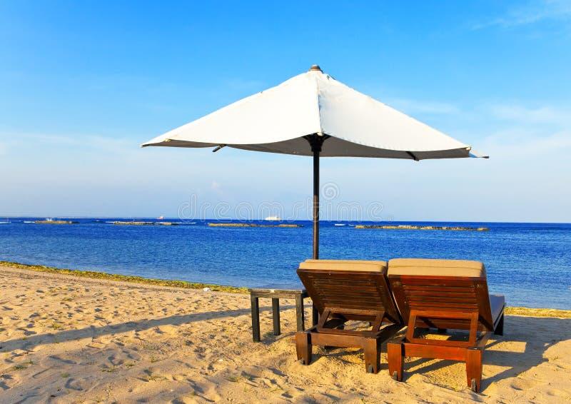 strandchaisen varar slö paraplyet arkivbild