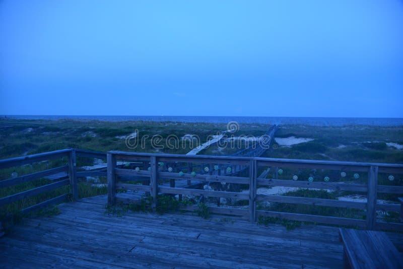 Stranddäcket på oceanfrontstugan är ett stort ställe som beskådar mörkret som faller på havvågorna royaltyfri foto