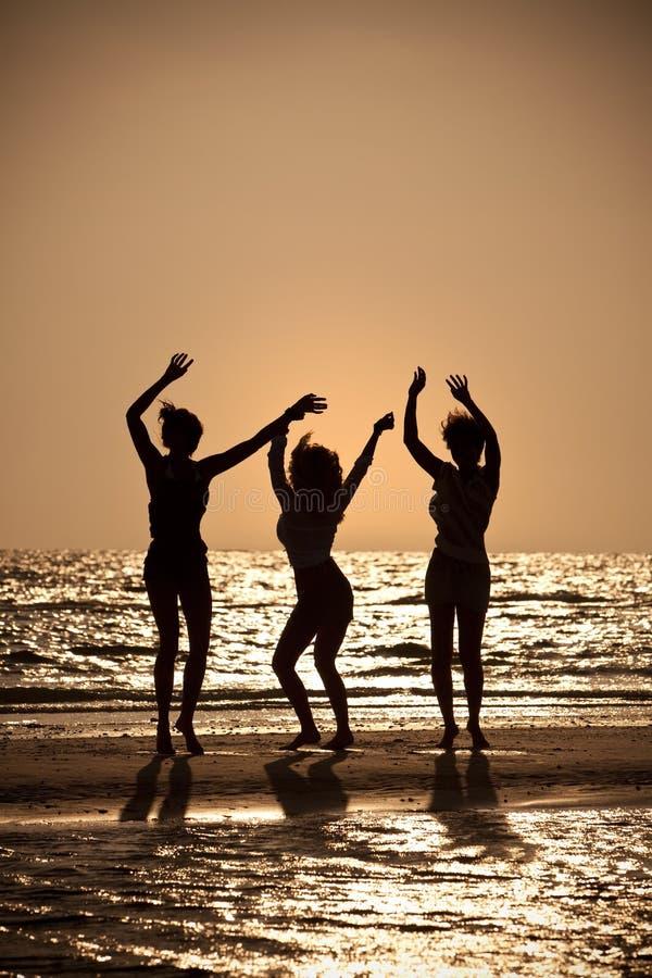 stranddanssolnedgång tre unga kvinnor royaltyfri fotografi