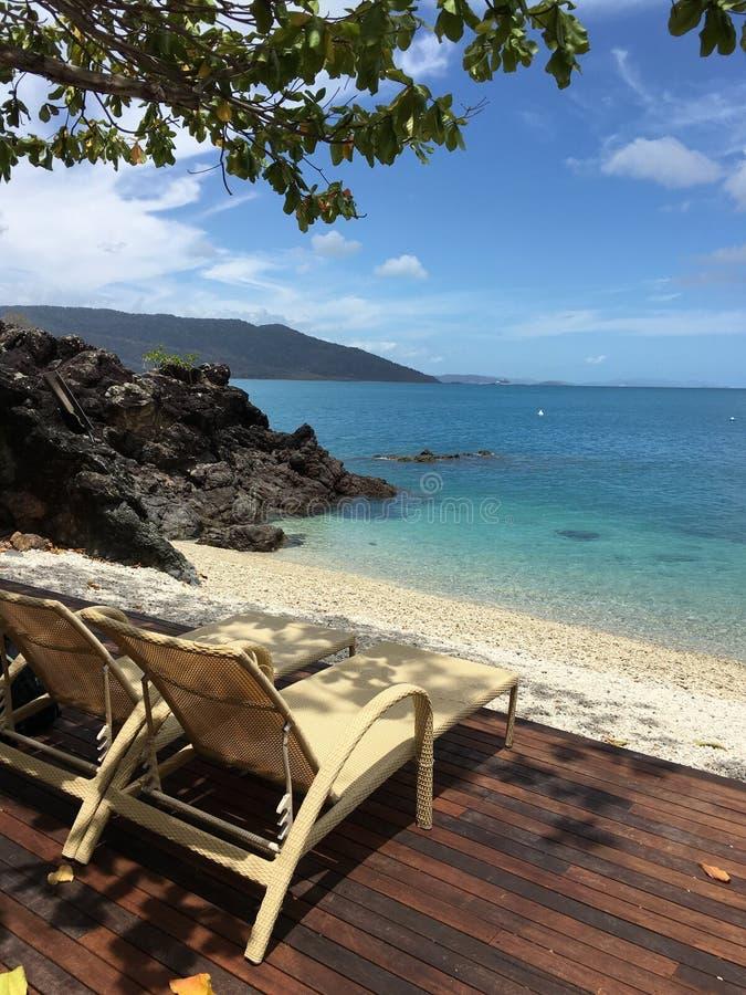 stranddek en stoel bij het strand van het dagdroomeiland airlie whitsundays stock afbeeldingen