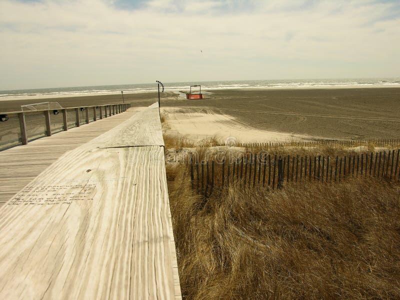 stranddyner över till walkwayen arkivbild
