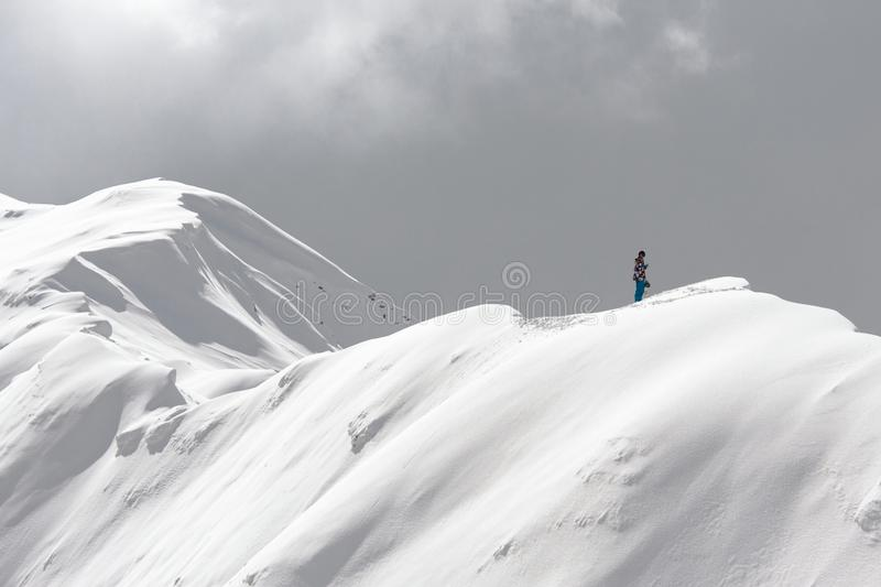 Stranded person standing on a snowy ridge at high altitude royalty free stock images