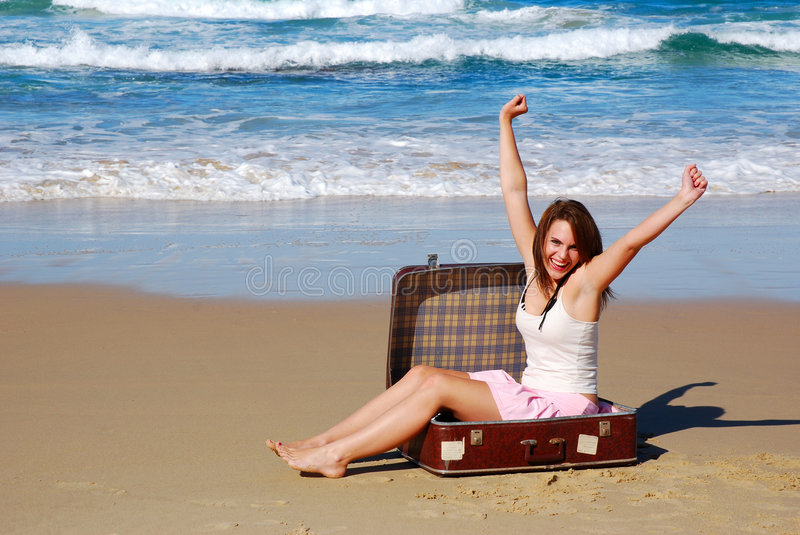 Stranded woman. Attractive young caucasian white woman with happy laughing facial expression sitting in her big brown suitcase and raising up her arms in the air