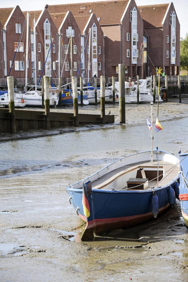 Stranded wooden boat on the mudflat at low tide in the port of h. Usum in germany, vertical, selected focus stock photo