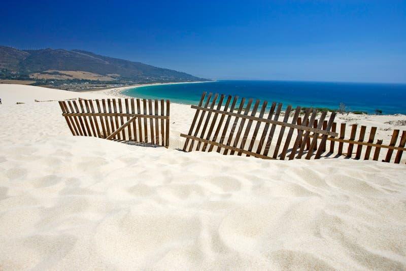 stranden deserterade dyner fäktar gammal ut sandig klibbning royaltyfri fotografi