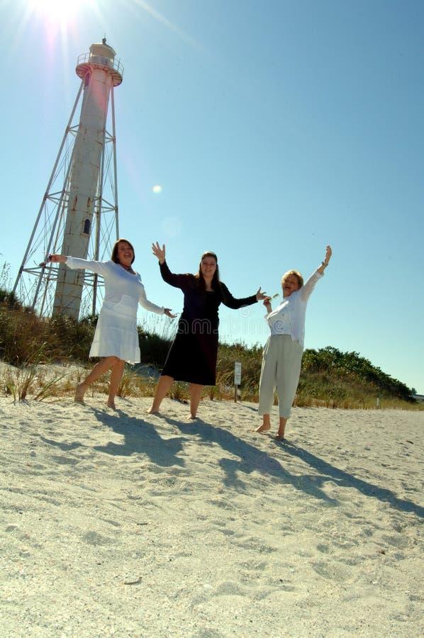 stranden firar semesterkvinnor royaltyfri bild