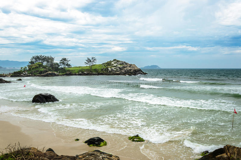 Stranden med något vaggar på sanden och en mini- ö på backgen fotografering för bildbyråer