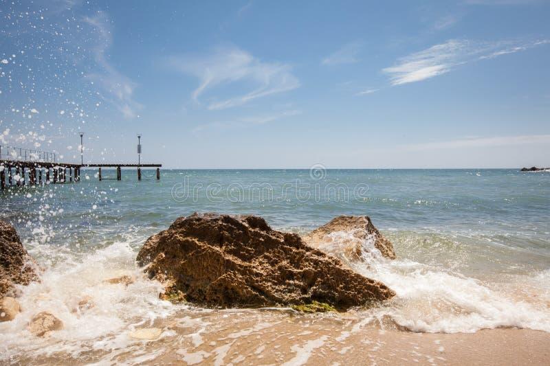 Stranden med vaggar och blå himmel Bakgrund för sommarsemester royaltyfria foton