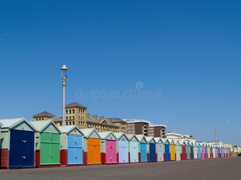 stranden nedanför blåa klara kojor fodrade upp skyen fotografering för bildbyråer