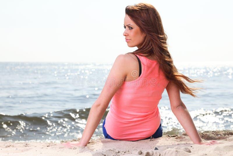 Stranden semestrar kvinnan som tycker om sanden för sommarsunsammanträde som ser ha royaltyfria foton