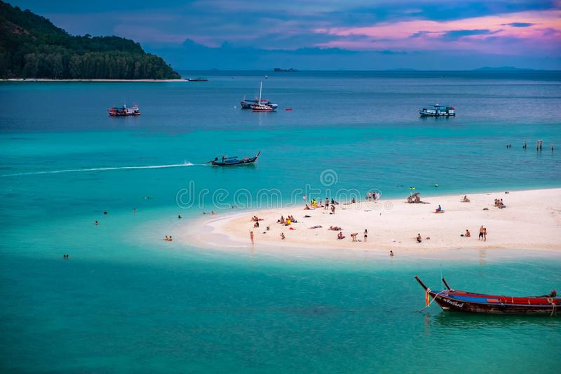 Stranden, som f?rdjupa in i havet som ut ser f?r att se ?n och den bl?a himlen, d?r ?r m?nga fartyg som sv?var i smaragdgr?splane arkivbilder