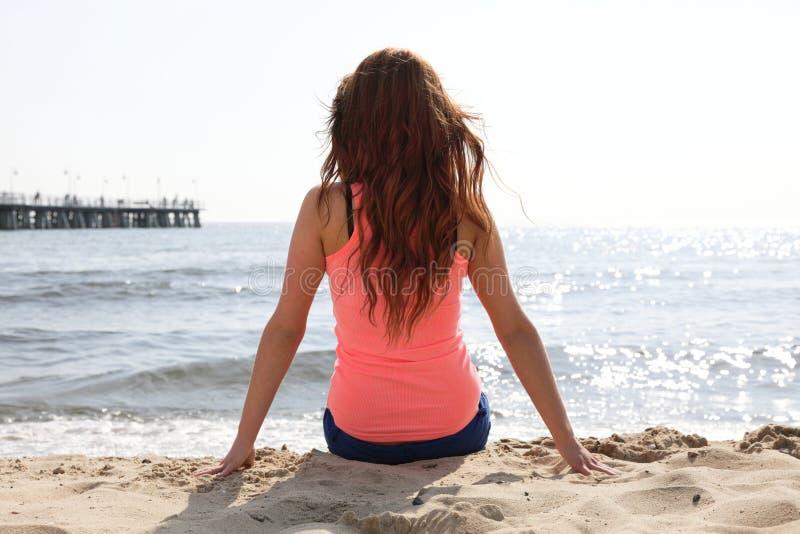 stranden som tycker om ferier som sitter sommar, sun kvinnan arkivbild
