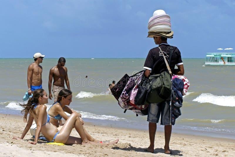 Strandförsäljare- och kvinnligsunbathers på stranden arkivbild