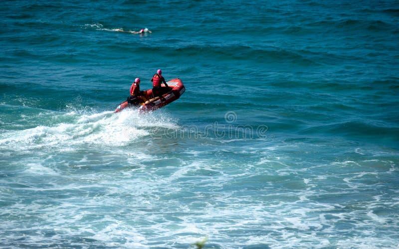 Strandförster auf einem roten Rettungsboot ein Surfer, der in der Nähe schwimmt lizenzfreie stockbilder