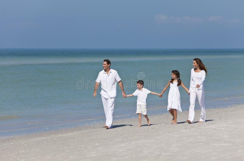 strandfamiljen hands att gå för holding royaltyfri foto