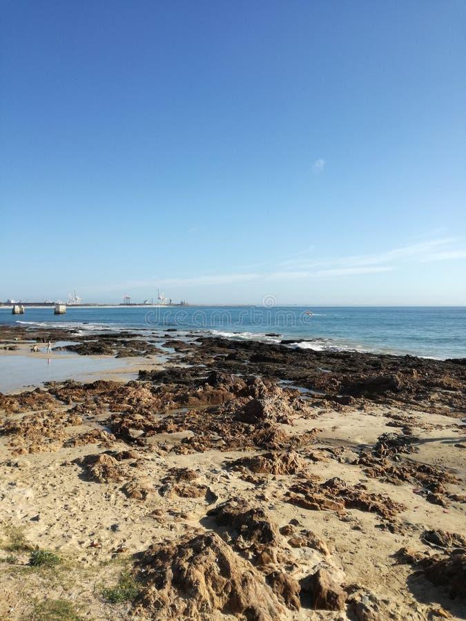 Strandfelsen-Sandufer stockbild