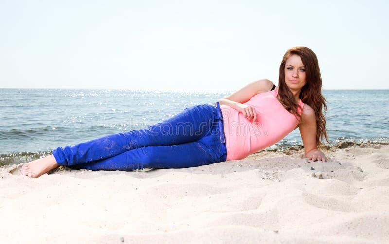 Strandferiekvinna som tycker om sommarsolsand som ser lycklig arkivfoton