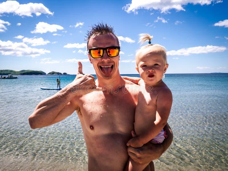 Strandferien: Ein Kerl in der Sonnenbrille auf dem Seeufer hält ein Kind in den Armen und zeigt das Symbol von Aloha Porträt lizenzfreies stockbild