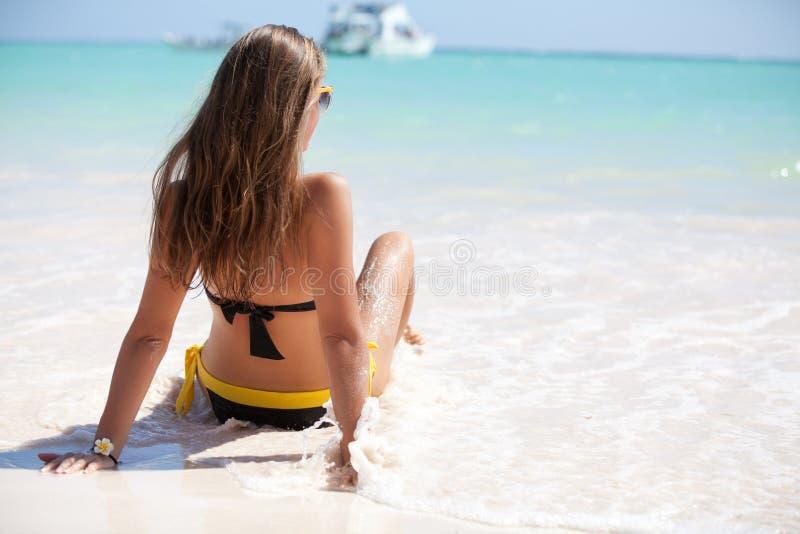 Strandferienfrau, die auf dem Sand glücklich sich entspannt stockbild
