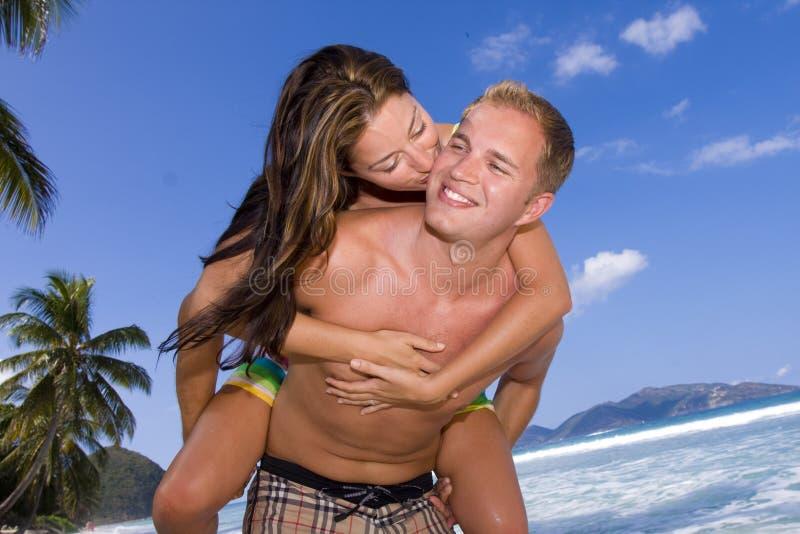 strandflickan ger henne kyssvännen royaltyfri bild
