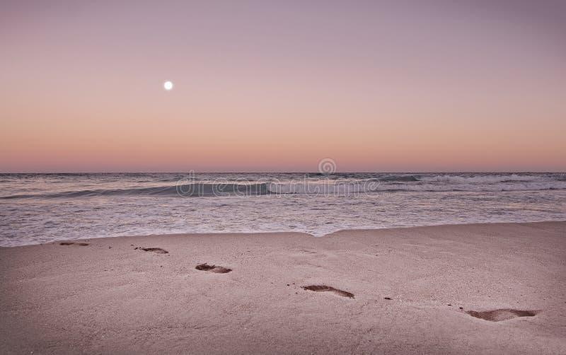 Strandfotspår i orange skymning som tonas, i att bo korall royaltyfria bilder