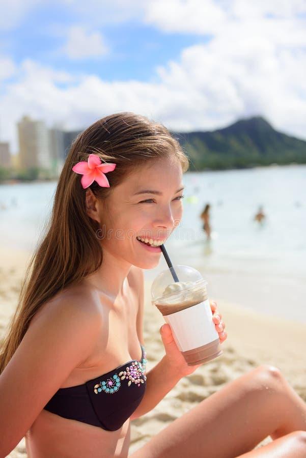 Strandfrau, die gefrorenes Kaffeecappuccinogetränk trinkt lizenzfreie stockbilder