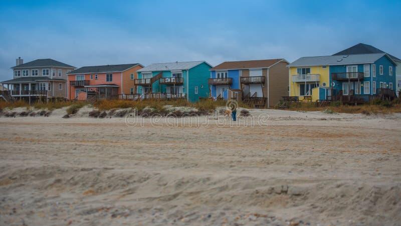 Strandhäuser mit Sand und Gras und Sturmwolken lizenzfreie stockfotografie