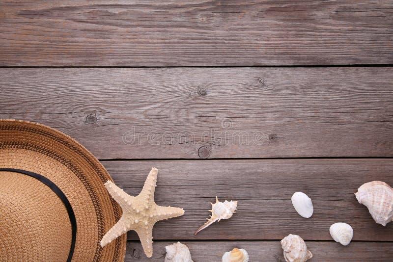 Strandhatt med snäckskal på den gråa trätabellen fotografering för bildbyråer