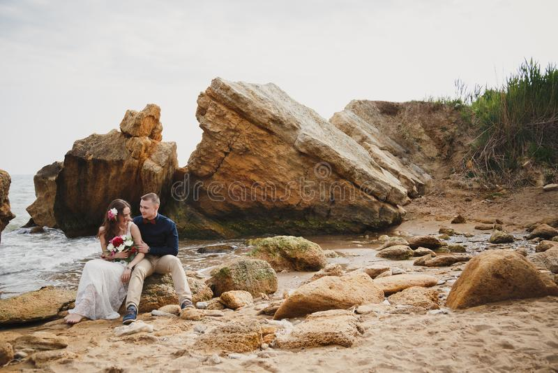 Strandhochzeitszeremonie im Freien nahe dem Ozean, romantisches glückliches Paar, das auf Steinen am Strand sitzt stockfotos
