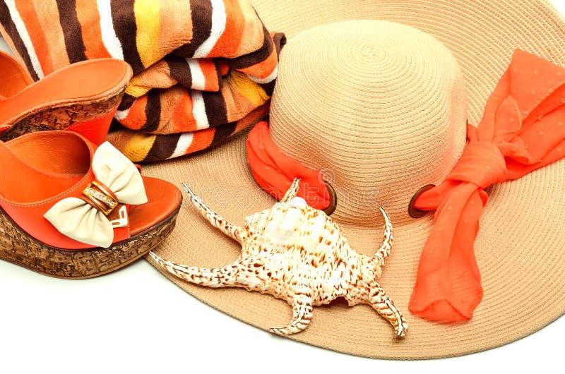 Strandhoed, handdoek, modieuze vrouwenschoenen en een zeeschelp royalty-vrije stock fotografie