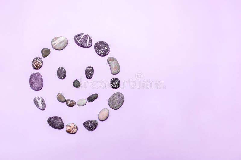 Strandkiesel machten in ein lächelndes Gesicht auf einem purpurroten Hintergrund Konzepte für Gesundheit, Glück, Heilung, Well stockfoto