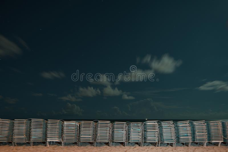 Strandklubsessel banden oben auf dem Sand nachts lizenzfreies stockbild