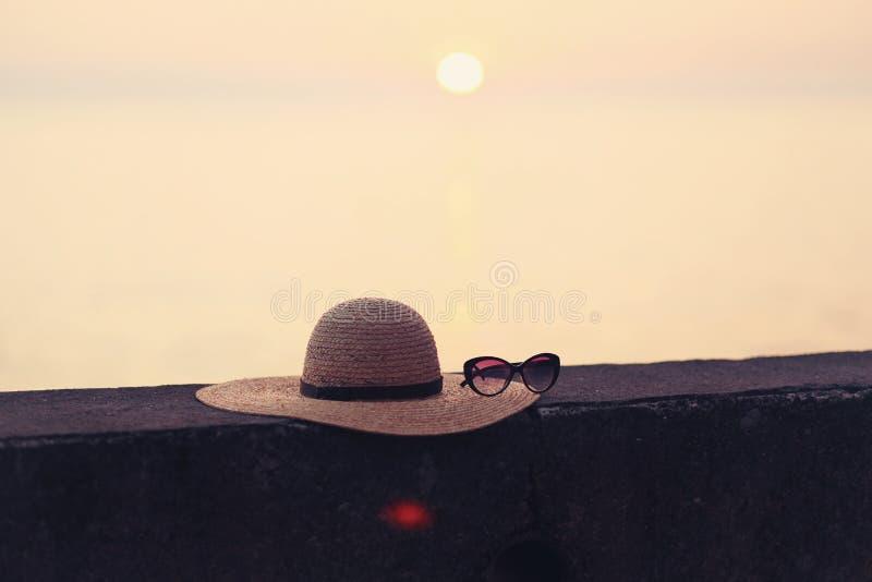 Strandkonzept - Sonnenbrille, Strohhut auf Asphalt mit Sonnenunterganglicht und Seehintergrundbeschneidungspfad lizenzfreie stockfotos