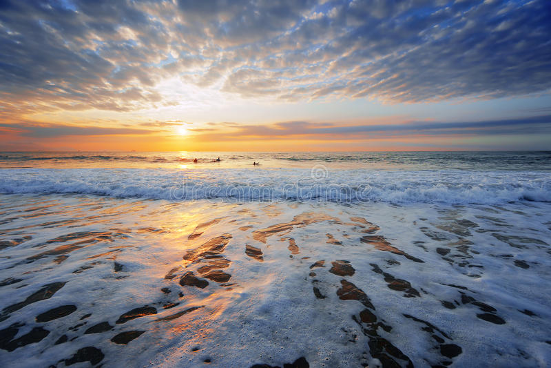 Strandkust bij zonsondergang met sommige surfers royalty-vrije stock foto's