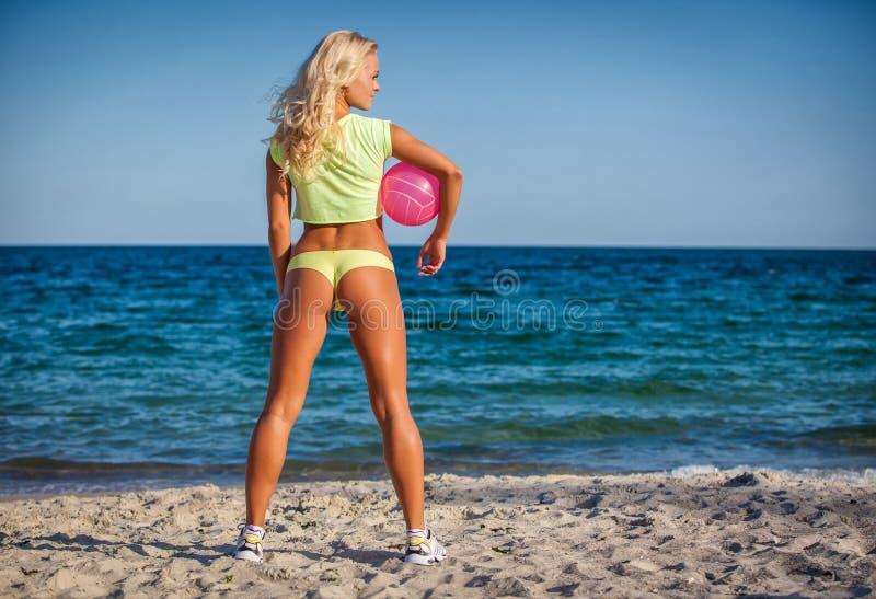 Strandkvinna i bikinin som rymmer en volleyboll royaltyfri fotografi