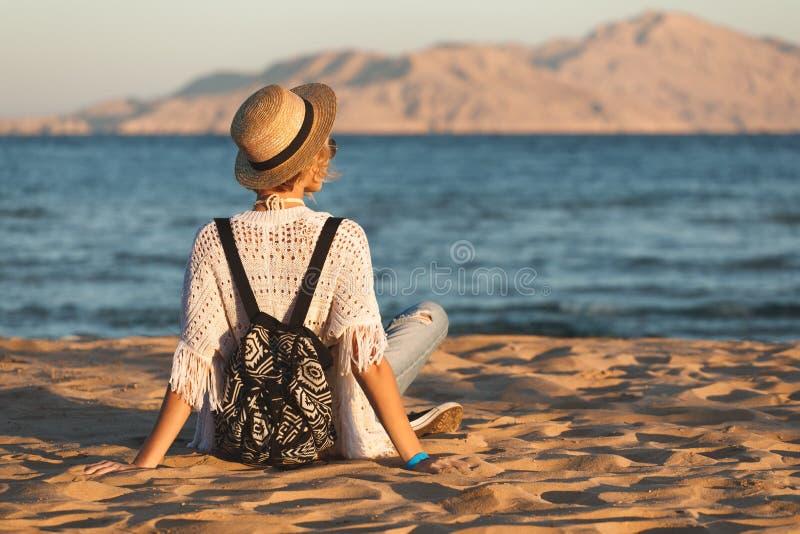 Strandkvinnan som är lycklig i hatten som har sommargyckel under loppferier, semestrar Flickan sitter på sanden och ser vattnet arkivfoton