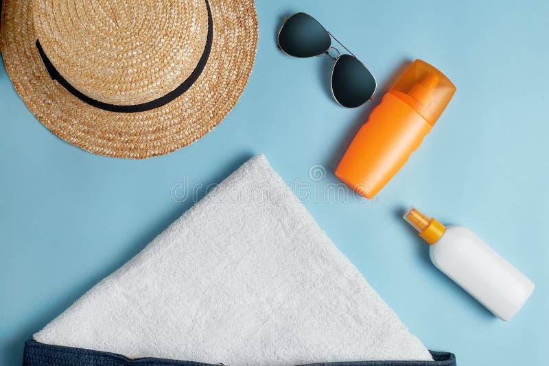 Strandlägenheten lägger tillbehör Solhatt, handduk, kräm, sunscreenflaska, solkräm, lotionflaska, snäckskal royaltyfria bilder