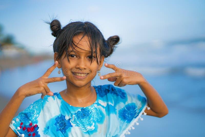 Strandlebensstilporträt des jungen schönen und glücklichen asiatischen Kindermädchens 8 oder 9 Jahre alt mit dem netten doppelten stockbild
