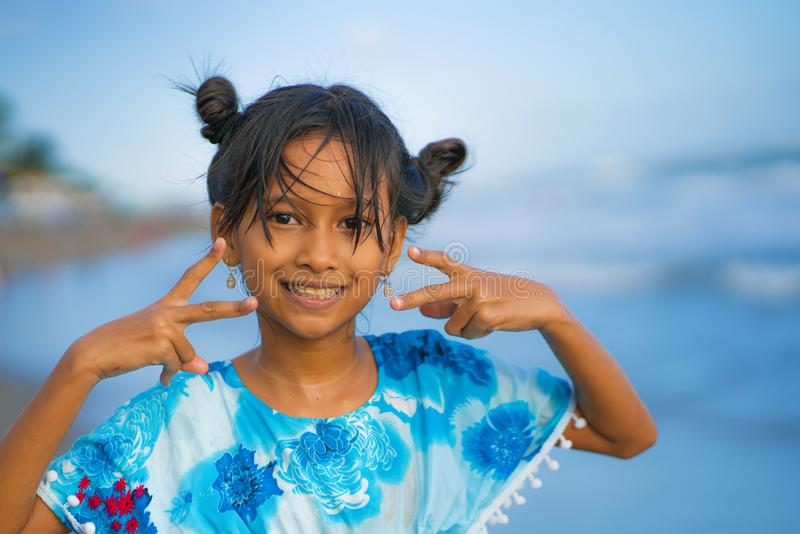 Strandlivsstilstående av den unga härliga och lyckliga asiatiska barnflickan 8 eller 9 gamla år med gulligt dubbelt spela för bul fotografering för bildbyråer